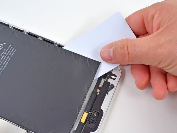 A plastic card makes a nice tool to pry the battery up from the rear panel, but it's still a very difficult task to break through all of the adhesive securing it to the rear case without puncturing the cells.