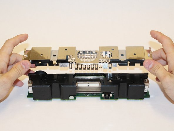 Lift the internal metal case from the plastic shell enclosing the heat sink assembly.