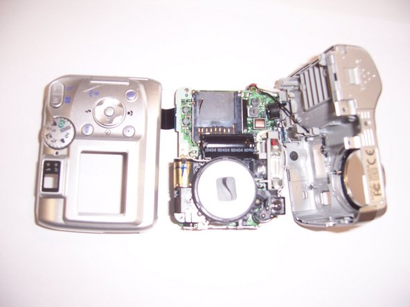 Pry apart the front outer casing from the circuit board. The camera will now be in three pieces.