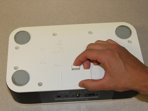 Remove the battery lid by pressing the battery cover's tab and pulling it away from the device.