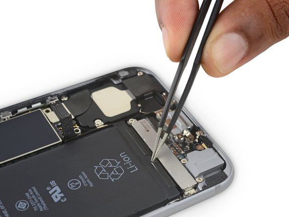 Use tweezers to peel back the tips of the two adhesive strips along the bottom edge of the battery.