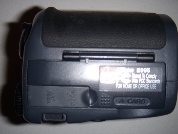 Set camera so the memory card compartment is facing you.