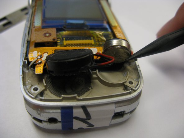 Using the spudger, carefully separate the black discs (speaker and microphone) from the inside surface of the phone.