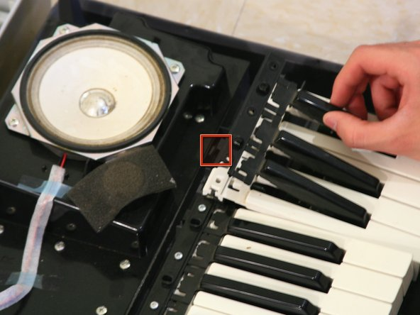 Press the tab on the back side of the block of keys out and detach the black keys.