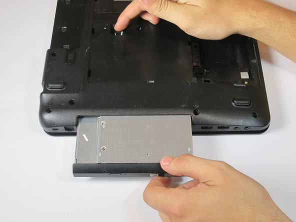 Image 2/2: The Disk Drive will begin sliding out of its slot. Remove Disk Drive from the laptop by hand.