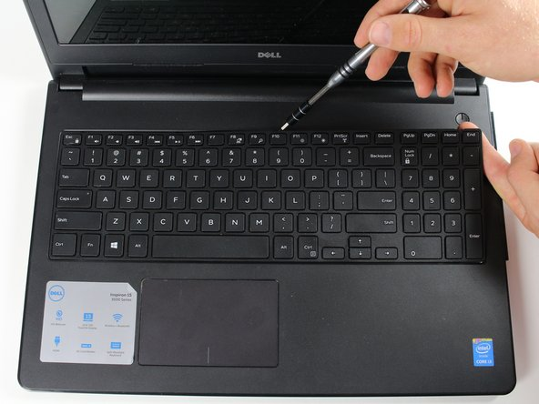 With the laptop open and facing upright, use the Spudger to pull at the notches shown in the image.