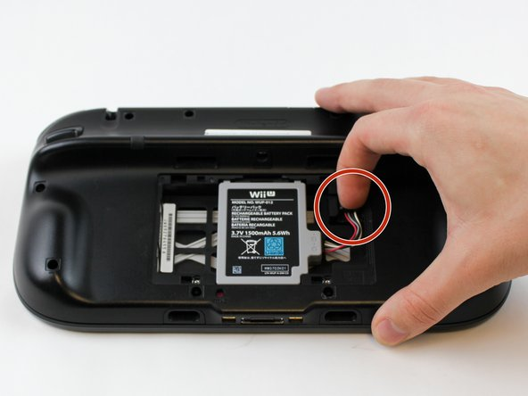 With your finger, press down and pull back on the battery connector plug.