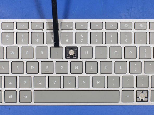 Image 1/1: To remove a key, wedge a plastic spudger under the key from the top most edge. Apply a bit of downward pressure on the spudger to lift the key. The key should make popping sounds and unlatch from the metal clips underneath the key that hold it to the keyboard frame.