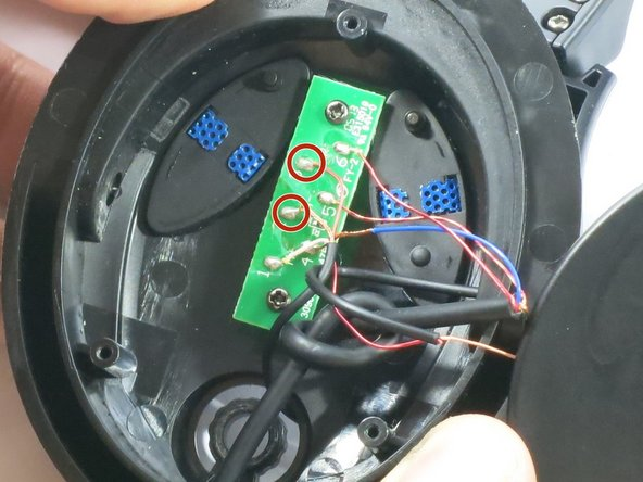 Apply heat to the circled wires on the circuit board with a heat gun.