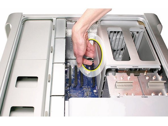 Image 1/1: Using your forefinger, reach below the fan and release the latch nearest the logic board.