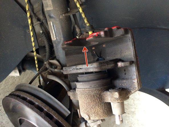 Den ausgebauten Bremssattel mit einem Band aufhängen, wegen des Bremsschlauches der abgeknickt werden kann. Alter Bremsbelag  am Kolben antfernen, dieser ist geklipst. Den zweiten Bremsbelag seitlich abziehen. Dann die Bremse mit einer Stahlbürste reinigen.