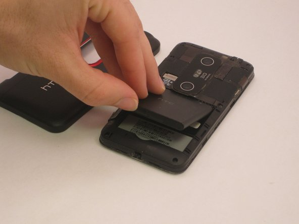 Remove the battery by pulling up on the lower indenture in the battery compartment.