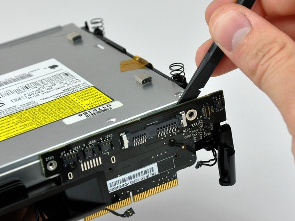 Use the flat end of a spudger to separate the interconnect board from the optical and hard drives.