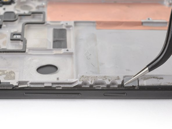 Use tweezers to lift the two silver retention brackets flanking either end of the volume and power buttons straight up and remove them from the phone.