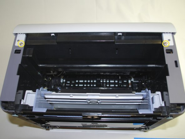 "Using a Phillips #2 screwdriver, remove the two, 1"" Phillips, PH#2 screws on the front face of the printer"