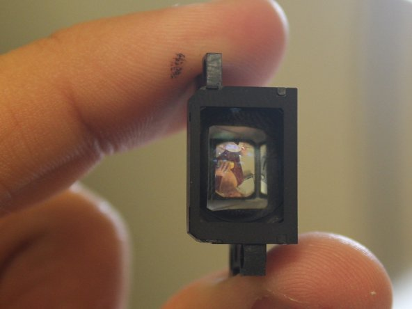 After removing the screws, the lens will just lift free from the black component.