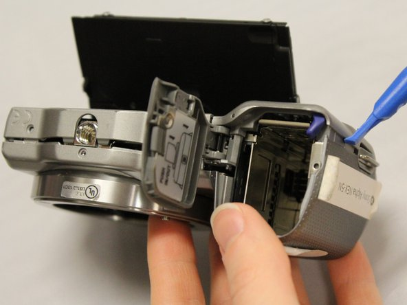 Hold the device with the lens facing you, and grasp the battery compartment.