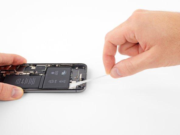 Tirez régulièrement, en exerçant une tension constante sur la bande jusqu'à ce qu'elle glisse hors de son emplacement entre la batterie et la coque arrière.