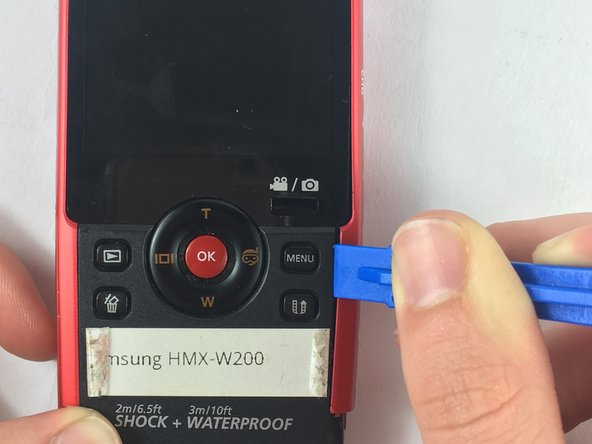 Using the plastic opening tool, separate and pull away the red casing on the right of the LCD screen.