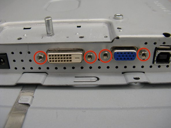 Use a 5 mm nut driver to remove the four 12 mm standoff screws securing the video connectors to the panel.