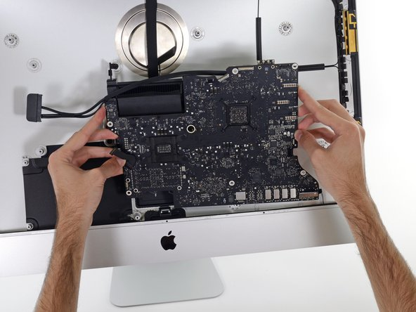 Lift the logic board straight up and out of the iMac. Be careful not to snag on any of the screw posts attached to the inside of the rear case.