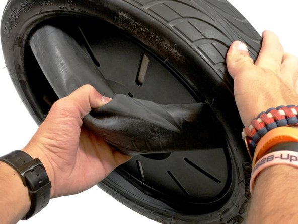 Pull out the inner tube as you rotate tire. The inner tube should be fully pulled out of the tire by the time you finish this step.