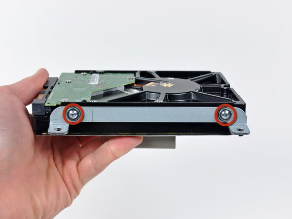 Remove the two T8 Torx screws securing the upper bracket to the hard drive.