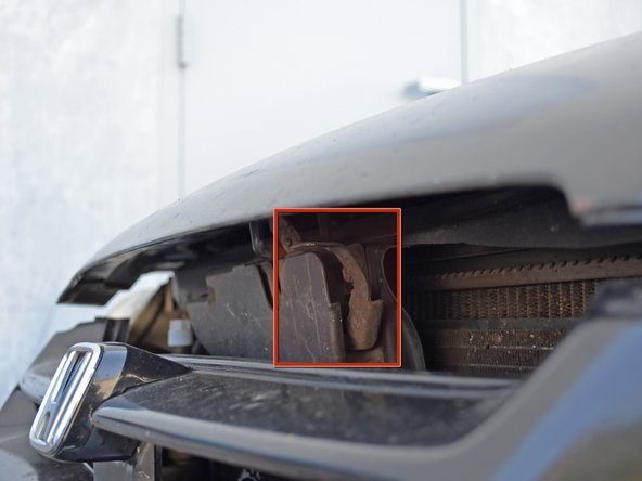 Image 2/3: Insert the hood prop rod into the hole in the hood marked with an arrow.