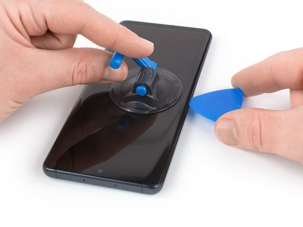 Once the screen is warm to the touch, apply a suction cup  to the left edge of the phone.