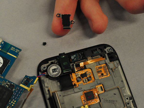 Image 1/3: Next, gently pull the Audio Output device off of the LCD touchscreen. It is secured by some weak adhesive and should come off easily.
