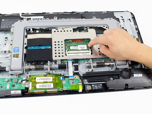 Pull apart the white tabs on the outside to release the RAM module.