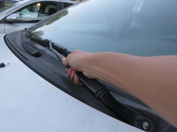 Image 2/2: Make sure to do this slowly so that your fingers are not compressed by the wiper arm and the windshield.