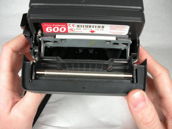 Remove old battery/ film cartridge from camera.