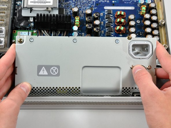 Image 2/3: The power supply requires a large amount of force to remove.  You may need to bend the edge of the front case toward yourself for enough clearance to remove the power supply.