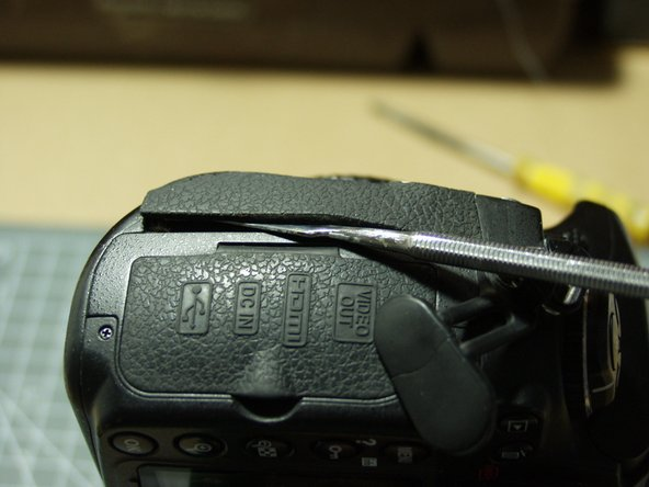 Remove the left hand grip, after turning the socket covers back out of the way. Remove dirt and adhesive residue. Cut the adhesive away from the socket hole before attaching. The rubber must be seated into the various body apertures, esp. behind the focus selection lever and beside the remote socket.