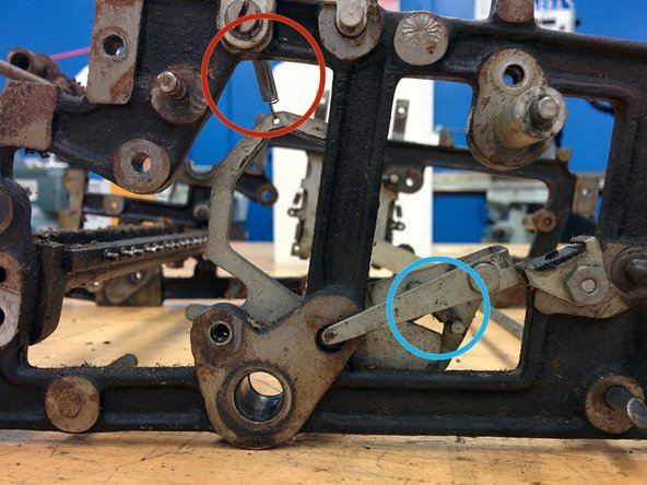 On the left side, unhook this spring from its post on the frame. Leave the other end on the part.