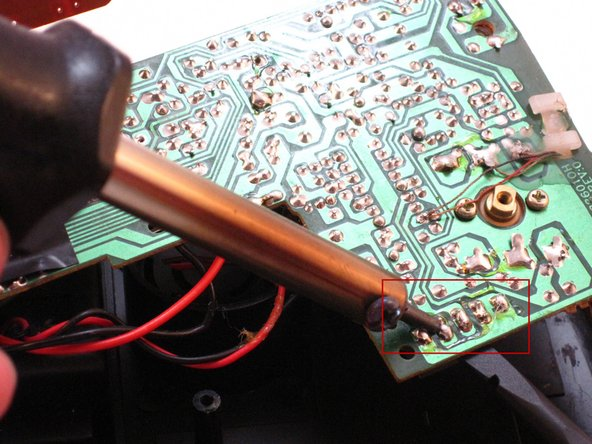 Carefully apply the hot soldering iron to the solder on top of the AM-FM pins.