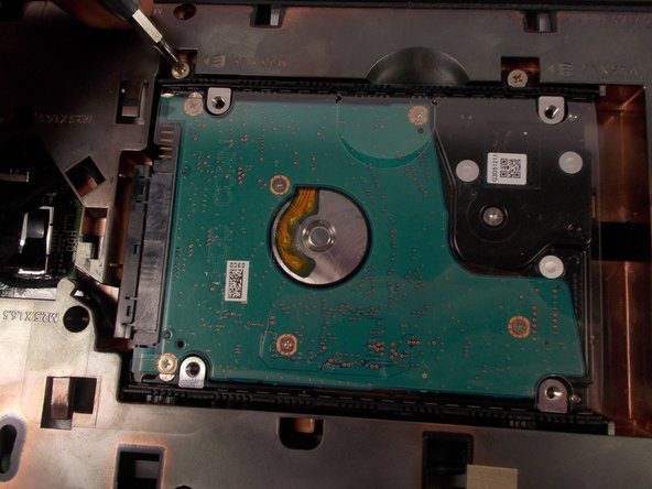 Remove the two silver phillips screws from the hard drive.