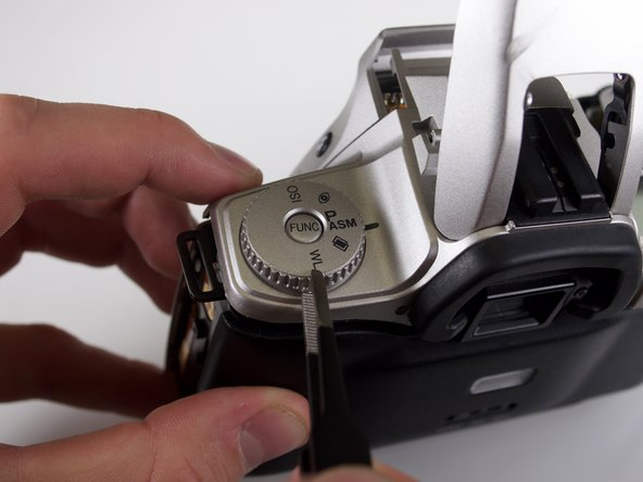 Using the tweezers, remove the dial from the top of the camera.