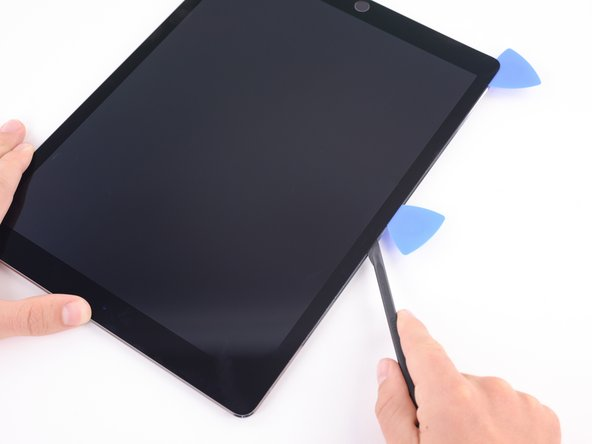 Image 2/3: Cut the adhesive along the upper left side of the iPad towards the front-facing camera using the halberd spudger. This may require reheating the edge of the iPad.