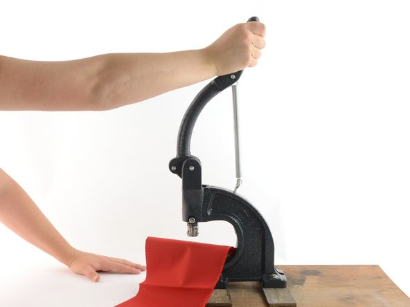 Image 1/3: With the fabric aligned, pull the handle of the hand press down in one continuous motion.