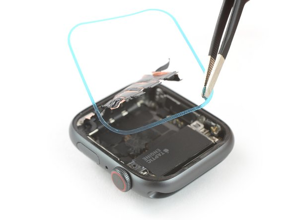 Hold the replacement adhesive diagonally to thread it over the display cable.