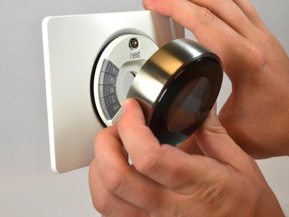 Image 2/3: Grasp the display's metal outer ring with your fingers and pull directly away from the wall, leaving the base behind.