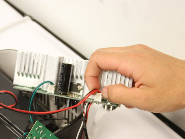Turn the circuit boards over. Remove the two connections on the left side by pulling on the tabs.