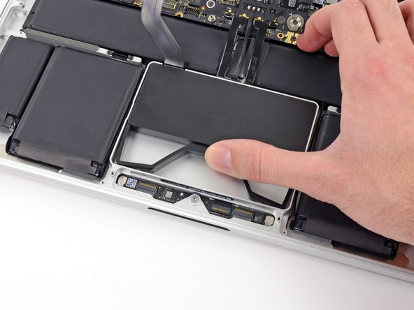 Image 2/3: While holding the spring bar depressed, tilt the SSD assembly up out of its cavity.