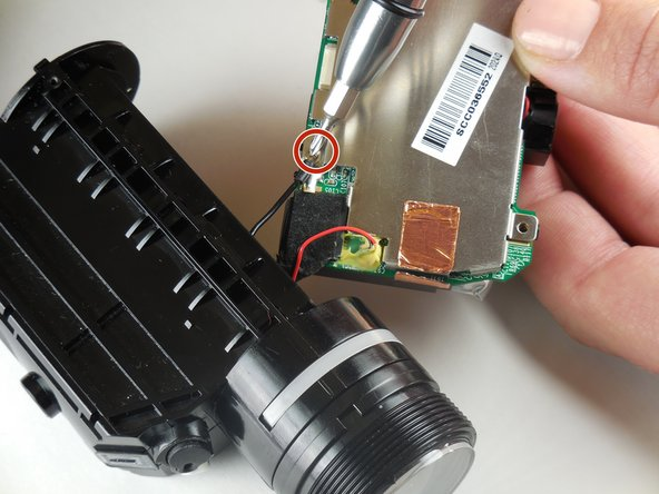 Using a phillips head screwdriver (PH 000), remove the screw connecting the lens unit to the logic board.