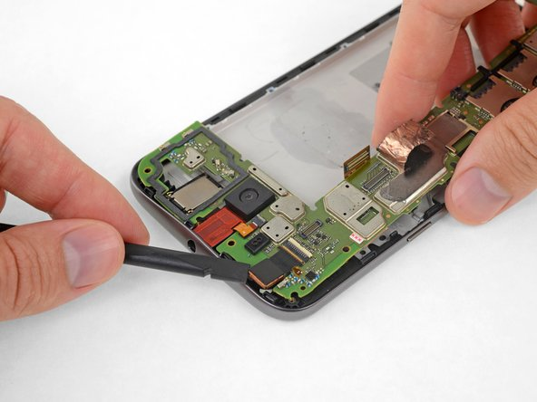 Grasping the motherboard by its edges, left the bottom end up at an angle, while keeping the top edge close to the phone.