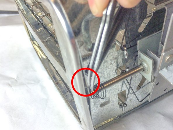 Insert the tweezers between the two metal flaps located at the top of the toaster.