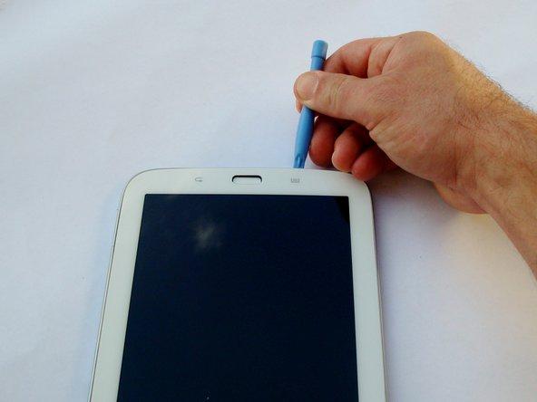 Schiebe das Werkzeug die Kante mit dem Home Button entlang, bis auch hier die Klebestellen frei sind.