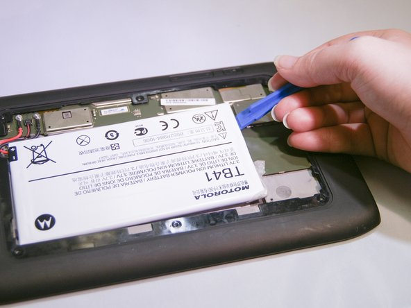Image 1/2: Some force is needed to lift the battery up because of the adhesive attached to the backside of the battery.